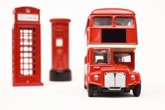 Postbox und rote Telefonzelle mit rotem Bus Stockbild
