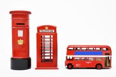Postbox und rote Telefonzelle mit rotem Bus Stockfotografie