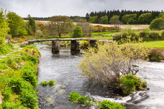 Postbridge Dartmoor National Park Devon. Ancient clapper bridge over the East Dart river at Postbridge in Dartmoor National Park in Devon UK Europe stock photos