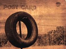 Postcard. Vintage Grunge Style Postcard With Tire on Fence Royalty Free Stock Photography