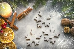 Postcard Christmas cookies in the form of flakes, decorated with dried orange, cinnamon sticks and anise, the background is sprink royalty free stock photo