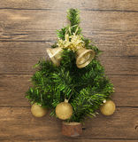Postcard with a Christmas tree ,Christmas balls, bells, and star on wooden background Stock Images