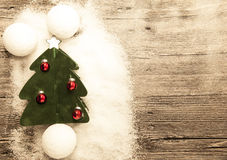 Postcard with a Christmas tree ,Christmas balls snowballs and snow on wooden background Royalty Free Stock Photography