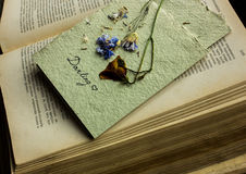 Postcard from dried flowers on an old book Stock Photos