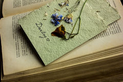 Postcard from dried flowers on an old book Stock Images