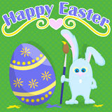 Postcard for Easter, funny cartoon Easter Bunny with paintbrush paint egg on a green background in peas and the words Happy Easter Stock Image