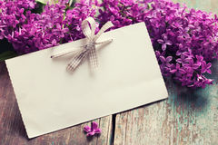 Postcard with elegant lilac flowers and empty tag for text Stock Images