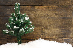 Postcard with a fir tree and snowflakes on wooden background Royalty Free Stock Photos