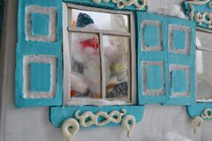 Postcard with funny Small Santa. Father Frost is looking out of the window with old shutters in Russian style Stock Photo