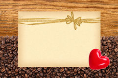 Postcard with golden bow on roasted coffee beans and wood Stock Images