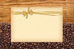 Postcard with golden bow on roasted coffee beans and wooden Royalty Free Stock Image