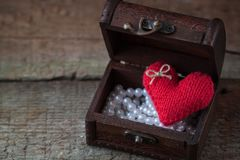 Postcard with handmade red knitted Valentine heart in the wooden chest on rustic background royalty free stock photography