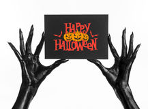 Postcard and Happy Halloween theme: black hand of death holding a paper card with the words Happy Halloween on a white isolated ba Royalty Free Stock Photo