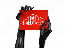 Postcard and Happy Halloween theme: black hand of death holding a paper card with the words Happy Halloween on a white isolated ba Stock Photos