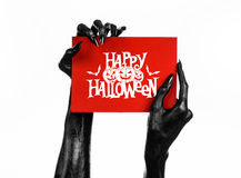 Postcard and Happy Halloween theme: black hand of death holding a paper card with the words Happy Halloween on a white isolated ba Royalty Free Stock Photography