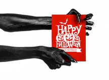 Postcard and Happy Halloween theme: black hand of death holding a paper card with the words Happy Halloween on a white isolated ba Stock Images