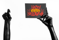 Postcard and Happy Halloween theme: black hand of death holding a paper card with the words Happy Halloween on a white isolated ba Stock Photo