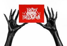 Postcard and Happy Halloween theme: black hand of death holding a paper card with the words Happy Halloween on a white isolated ba. Ckground Stock Photo