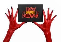 Postcard and Happy Halloween theme: red devil hand with black nails holding a paper card with the words Happy Halloween on a white Stock Image
