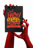 Postcard and Happy Halloween theme: red devil hand with black nails holding a paper card with the words Happy Halloween on a white Royalty Free Stock Image