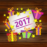 Postcard Happy New Year and Merry Christmas with gifts on the background of wood texture. Stock Photos