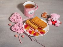 Postcard Happy Valentine`s Day. Pink dishes, decor and Viennese waffles with a mug of tea. royalty free stock photos