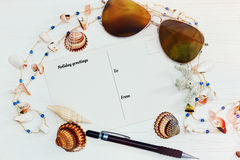 Postcard with holiday greetings on the white table with sea shel. Top view still life with post card, sunglasses, necklace and sea shells on the rude painted Royalty Free Stock Photography