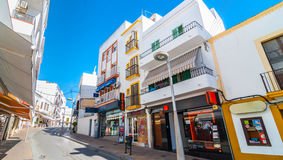 Postcard from Ibiza, brilliant sunny bright streets of St Antoni de Portmany Balearic Islands, Spain. Shops, parlors, cafes and convenience stores line bright Royalty Free Stock Photos