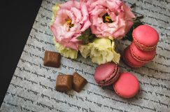 Postcard macaroons and flowers with chocolate, on white paper stock photo