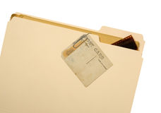 Postcard on Manila Folder. An old and stained post card paper clipped to a manila folder with a few negative strips just inside folder. Isolated on a white royalty free stock photo