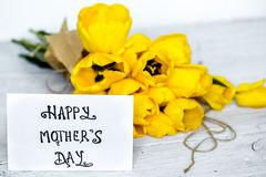 Postcard Mother`s Day and yellow tulips on wooden background Royalty Free Stock Photos