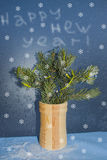 Postcard for the New year. With a fir branch on a background of frosty Windows Stock Image
