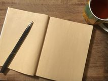 Postcard or note paper with notebook on wooden brown background stock photos