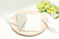 Postcard on pink plate with white ribbon, grey envelope and white flowers stock photo