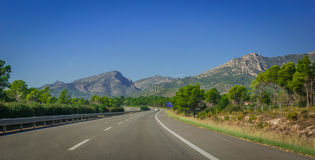 Postcard from Spain.  Lone car goes down the highway through coastal foothills and mountains of Spain. Sunshine on Coastal highway.  Lone white car drives along Royalty Free Stock Photo