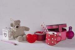 The Postcard to Valentine`s day with teddy bear, cup in the dots, light and casket on white wooden background. Postcard to Valentine`s day with teddy bear, cup stock image