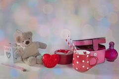 The Postcard to Valentine`s day with teddy bear, red cup in the dots, light and casket on white wooden background. Postcard to Valentine`s day with teddy bear stock images