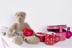 The Postcard to Valentine`s day with teddy bear, red cup in the dots, light and casket on white wooden background. Postcard to Valentine`s day with teddy bear royalty free stock photography
