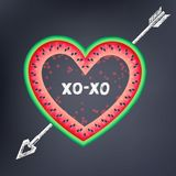 Postcard to the Valentine`s Day with text. `XOXO`. Heart on watermelon pierced by a chalk arrow on a dark background Royalty Free Stock Images