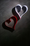 Postcard to Valentine's Day. White and red heart made of paper strips. Dark background. Royalty Free Stock Photo