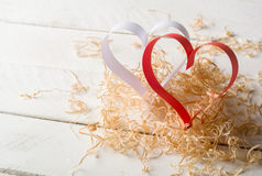 Postcard to Valentine's Day. White and red heart made of paper strips. Decorative curly wood shavings Royalty Free Stock Photo