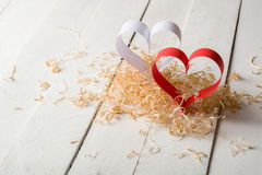 Postcard to Valentine's Day. White and red heart made of paper strips. Decorative curly wood shavings Stock Photos