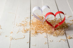 Postcard to Valentine's Day. White and red heart made of paper strips. Decorative curly wood shavings Royalty Free Stock Photography