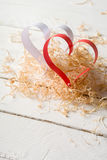 Postcard to Valentine's Day. White and red heart made of paper strips. Decorative curly wood shavings Stock Images