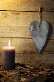 Postcard with a wooden heart and candle light Stock Images
