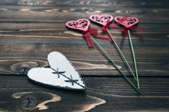 Postcard with wooden white heart and blurring decorative flowers on background Royalty Free Stock Photos