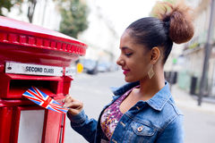 Postcard. Young woman posting a postcard in London Stock Photography