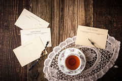 Postcards with cup of tea on the wooden table horizontal. Postcards with cup of tea , lace napkin ,pen and watch  on the wooden table horizontal Royalty Free Stock Images