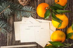 Postcards with fir tree and mandarins on the wooden table Stock Photography