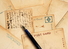 Postcards with fountain pen. An array of antique postcards with a fountain pen, one featuring Japanese writing Stock Photo